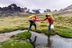 男性爬山者在秘鲁的安地斯帮助伙伴穿过一条河 免版税库存图片