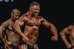 男性爱好健美者拉伤他的吸收和胸口肌肉 免版税库存图片