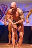 男性爱好健美者显示力量并且显示他的最佳的体质 免版税库存图片