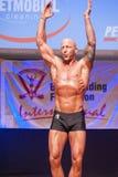 男性爱好健美者显示他的最好在阶段的冠军 库存照片