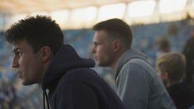 男性爱好者在体育场急切地观看体育比赛,高兴胜利和容忍 股票视频