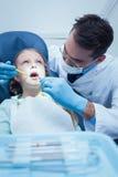 男性牙医审查的女孩牙 免版税库存图片