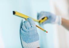 男性特写镜头在测量有磁带的手套的墙壁 库存图片