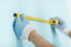 男性特写镜头在测量有磁带的手套的墙壁 免版税图库摄影