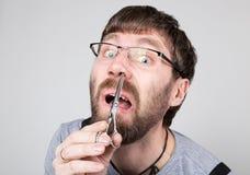男性理发师剪他在鼻子的自己的头发,看象镜子的照相机 时髦的专业美发师 免版税库存图片