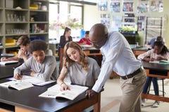男性生物课的高中家庭教师教的学生 免版税图库摄影