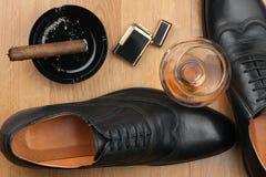 男性生活方式 鞋子、雪茄、打火机和酒精 图库摄影