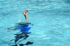 男性男孩奋斗水下淹没在游泳场 免版税库存照片