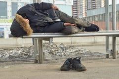 男性睡觉在公共汽车站的被喝的叫化子 免版税库存照片