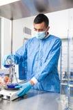 男性科学家与绞拌器一起使用在实验室礼服 免版税库存图片