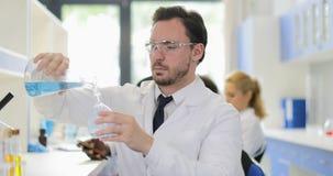 男性科学家倾吐在看在工作在化工实验室穿戴白色外套和防护玻璃的烧瓶的液体 影视素材