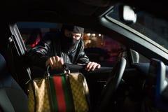 男性窃贼窃取从汽车的袋子在停车处 库存照片