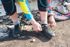 男性竟赛者mtb骑自行车者为栓鞋带的种族做准备 库存照片
