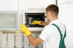 男性管理员清洁微波炉 免版税库存图片