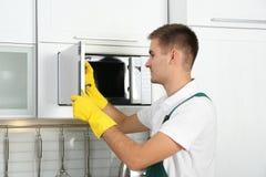 男性管理员清洁微波炉 库存照片