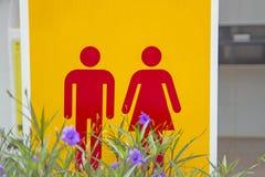 男性红女性洗手间标志,与紫色flo的黄色背景 库存图片