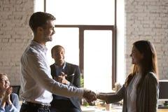 男性组长握手女性激动的雇员congratulat 免版税库存照片