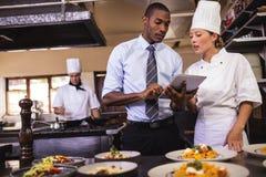 男性经理和使用数字片剂的女性厨师在厨房 免版税库存图片