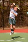 男性网球员在飞跃进行到底顶上的射击 免版税库存照片
