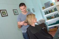 男性美发师做女孩的发型在发廊 库存图片