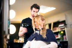 男性美发师的年轻白肤金发的女孩 免版税库存图片