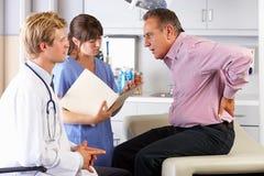 男性耐心的访问的医生的Office With后背疼痛 免版税库存图片