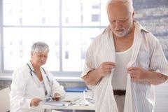 男性耐心脱下衣服在医生的空间 免版税库存图片