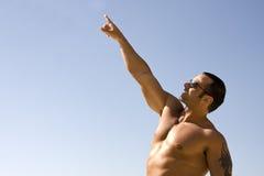 男性肌肉指向的天空年轻人 免版税库存图片
