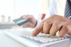 男性胳膊拿着信用卡按钮 免版税库存图片