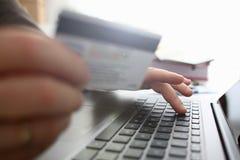 男性胳膊拿着做调动的信用卡按钮 库存图片