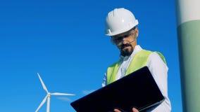 男性能学工作者站立与他的膝上型计算机在风轮机附近 干净,eco友好的能量概念 股票视频