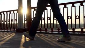 男性脚沿一座现代桥梁努力去做在慢动作的精采日落 影视素材
