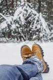 男性腿特写镜头在蓝色牛仔裤和冬天鞋子的在雪 免版税库存照片
