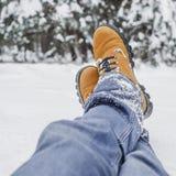 男性腿特写镜头在蓝色牛仔裤和冬天鞋子的在雪 免版税库存图片