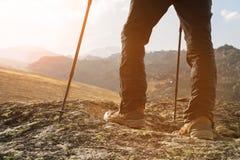 男性腿特写镜头在迁徙的起动的用遥远的北欧人的棍子走以岩石为背景和 免版税库存图片