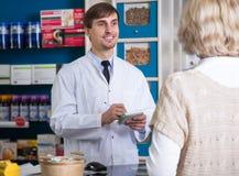 男性药剂师谈话与顾客在药房 图库摄影