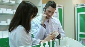 年轻男性药剂师谈话在手机,当检查在药房时的处方 股票视频