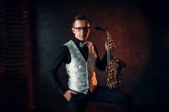 男性萨克斯管吹奏者摆在与萨克斯管的,爵士乐人 库存图片