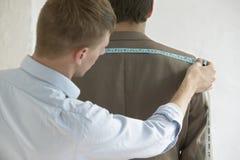 男性裁缝测量的顾客的衣服 免版税库存照片