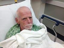 男性资深住院病人在医院病床上 免版税库存照片