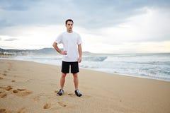 年轻男性赛跑者在站立在沙子的白色T恤杉穿戴了休息在密集的早晨凹凸部以后 库存图片