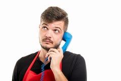 男性超级市场雇主谈话与大蓝色电话接收器 免版税库存照片