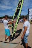 男性辅导员显示如何处理风帆冲浪在海滩 免版税库存照片