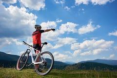 男性运动专业骑自行车的人身分后面看法与越野自行车的在小山顶部 免版税库存照片