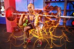 男性运动员举重在健身演播室 库存图片
