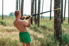 男性运动员优秀训练训练圈,新鲜空气自然在夏天森林,感觉您的力量,刺激 免版税库存照片