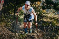 男性运动员在森林远足与北欧人走的杆的traill 图库摄影