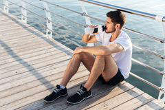 男性运动员坐码头和饮用水 库存图片