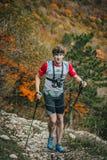 年轻男性运动员是在与拐杖的一个山行迹 免版税库存图片