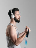 年轻男性运动员训练二头肌侧视图画象干涉与抵抗带 免版税库存照片